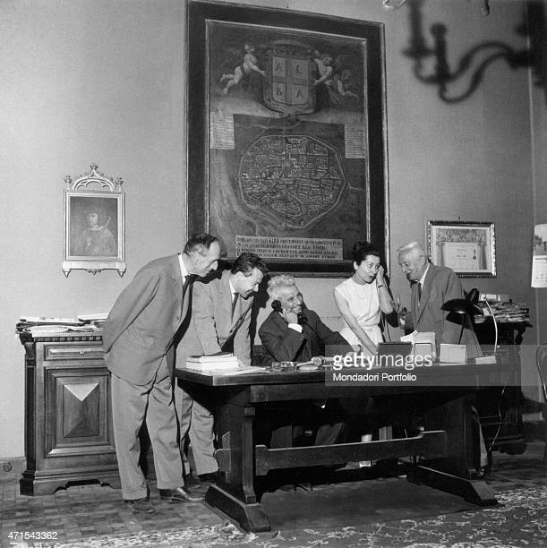 The mayor Osvaldo Cagnasso checking the functioning of his telephone sitting at the desk in his office surrounded by his collaborators his council is...