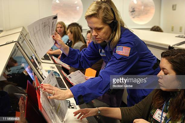The McAuliffe Center at Framingham State University trained teachers on space simulators Flight director Elsa Oberg works with the teachers on right...