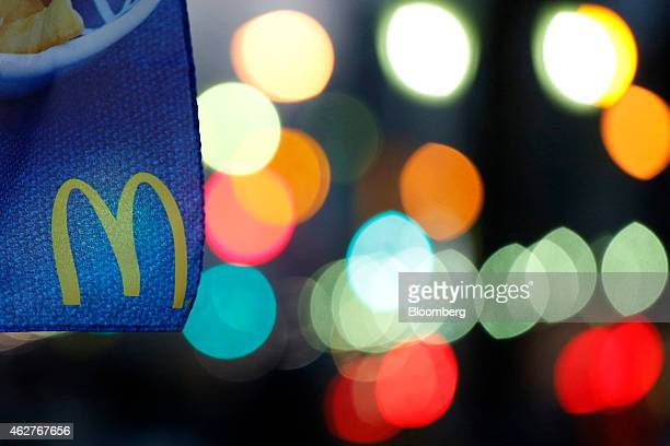 The McDonald's Corp logo is displayed on a banner outside a McDonald's restaurant operated by McDonald's Holdings Co Japan Ltd at dusk in Tokyo Japan...