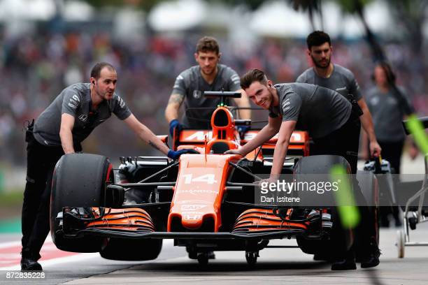 The McLaren Honda team push the car of Fernando Alonso of Spain and McLaren Honda in the Pitlane during final practice for the Formula One Grand Prix...