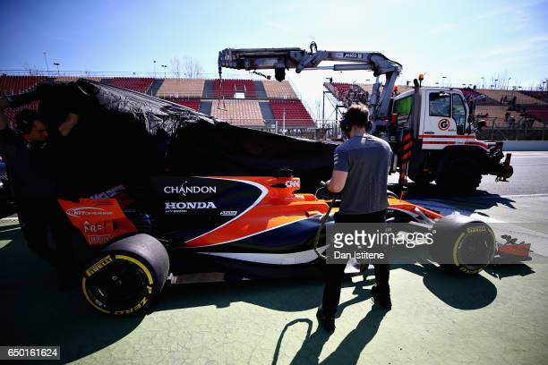 The McLaren team cover the car of Stoffel Vandoorne of Belgium and McLaren Honda after it stopped on track during day three of Formula One winter...