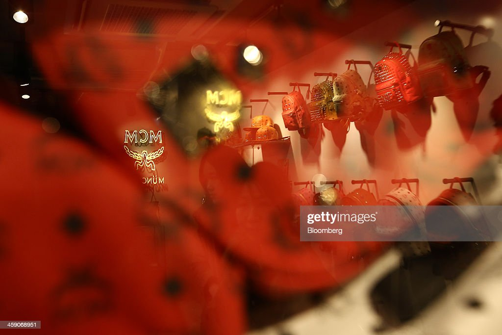 The MCM Holdings AG logo is seen reflected in a window at the company's store on Garosugil street in the Gangnam district of Seoul, South Korea, on Sunday, Dec. 22, 2013. Consumer prices climbed 0.9 percent in November from a year earlier after a 0.7 percent increase in October that was the smallest gain since July 1999. Photographer: SeongJoon Cho/Bloomberg via Getty Images