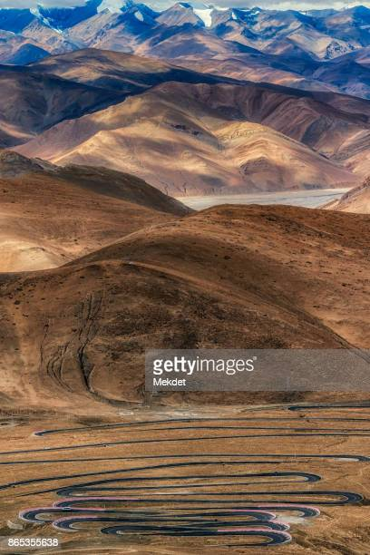 The meandering road to the mountain pass with the spectacular view of Himalayas Mountain Range of Tibet