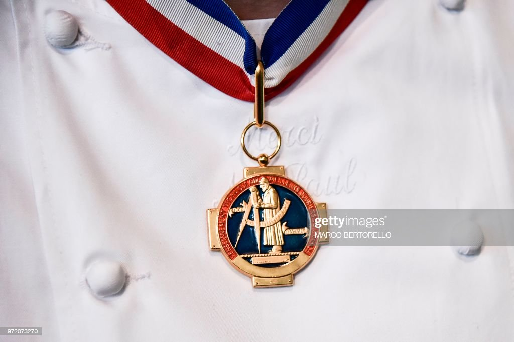 The medal of Paul Bocuse's academy is pictured on the chest of a French chef during the event of the Bocuse d'Or Europe 2018 International culinary competition, on June 12, 2018 in Turin.