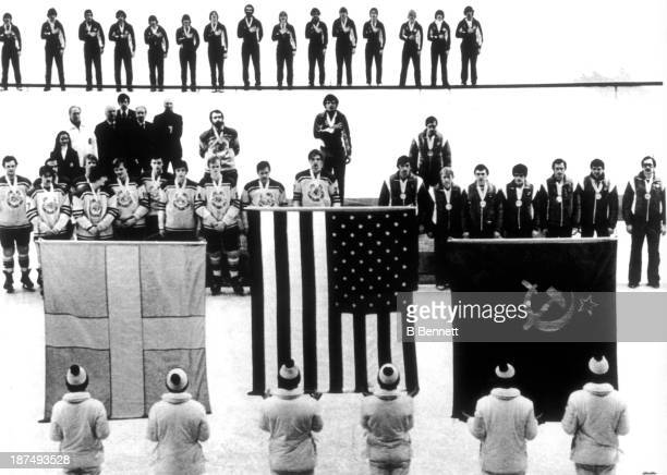 The medal winning teams in the Olympic hockey competition line up for the singing of the national anthems during the presentation ceremonies for the...
