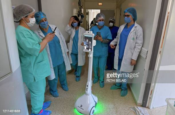 The medical staff at the Mami hospital interact with a robot, manufactured by a Tunisian company and donated to the hospital to support their efforts...