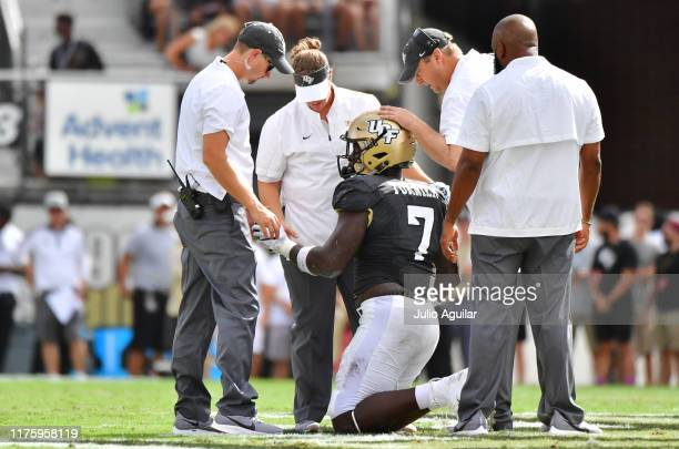 The medical team and Head coach Josh Heupel of the UCF Knights check on Kenny Turnier after an injury during the first quarter of a football game at...
