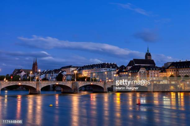 the medieval mittlere rheinbrücke (a stone brigde over river rhine) and church martinskirche with view to skyline of basel illuminated at dusk. basel, canton basel-stadt, switzerland. - stadt stock pictures, royalty-free photos & images