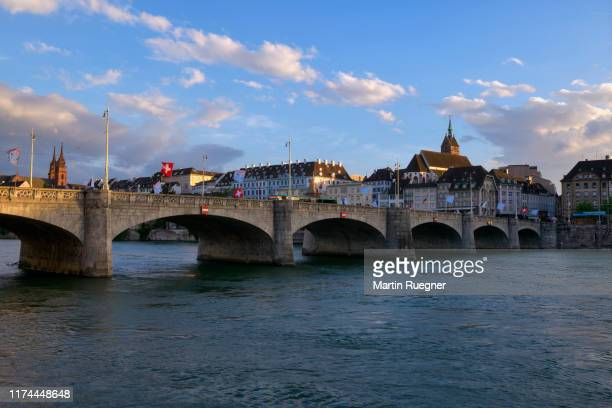 the medieval mittlere rheinbrücke (a stone brigde over river rhine) and church martinskirche with view to skyline of basel at sunset, dusk. basel, canton basel-stadt, switzerland. - basel switzerland stock pictures, royalty-free photos & images