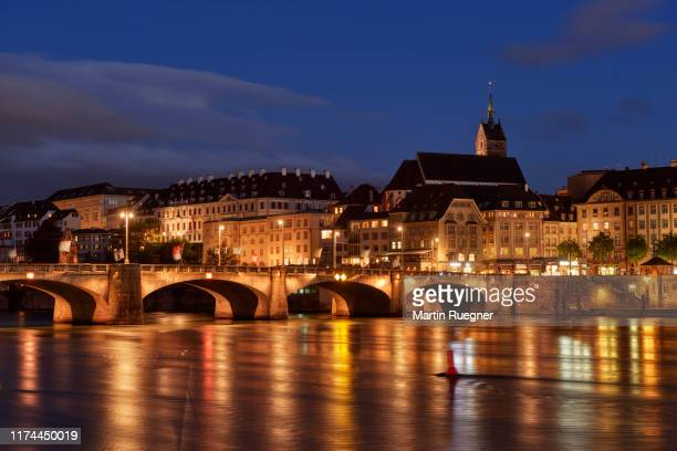the medieval mittlere rheinbrücke (a stone brigde over river rhine) and church martinskirche with view to skyline of basel illuminated at dusk. basel, canton basel-stadt, switzerland. - basel switzerland stock pictures, royalty-free photos & images
