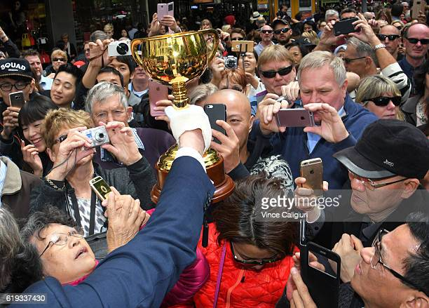 The Melbourne Cup is held into the crowd for fans to take pictures during the 2016 Melbourne Cup Parade on October 31 2016 in Melbourne Australia