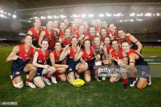The Melbourne girls celebrate winning the women's exhibition AFL match between the Western Bulldogs and the Melbourne Demons at Etihad Stadium on...