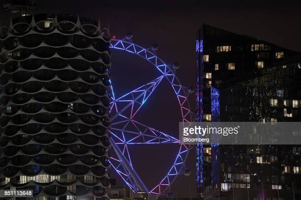 The Melbourne Star observation wheel is seen between residential buildings at night in the Docklands area of Melbourne Australia on Thursday July 20...