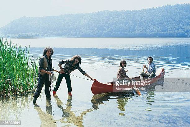 The members of Italian band The Pooh in a photocall shooted by the lake. From the left Red Canzian and Stefano D'Orazio pushing a canoe carrying Roby...