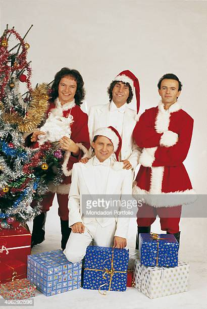 The members of Italian band The Pooh in white dinner suit posing smiling for a Christmas photocall shooted at the studio beside a Christmas tree and...