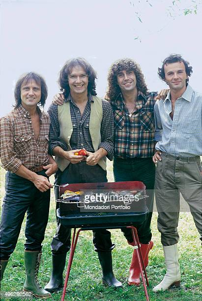 The members of Italian band The Pooh posing smiling beside a barbecue during a photocall shooted by the lake. From the left Roby Facchinetti , Red...