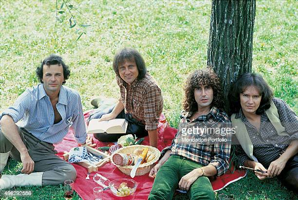 The members of Italian band The Pooh posing smiling while picnicking on the grass Photocall From the left Dodi Battaglia Roby Facchinetti Stefano...