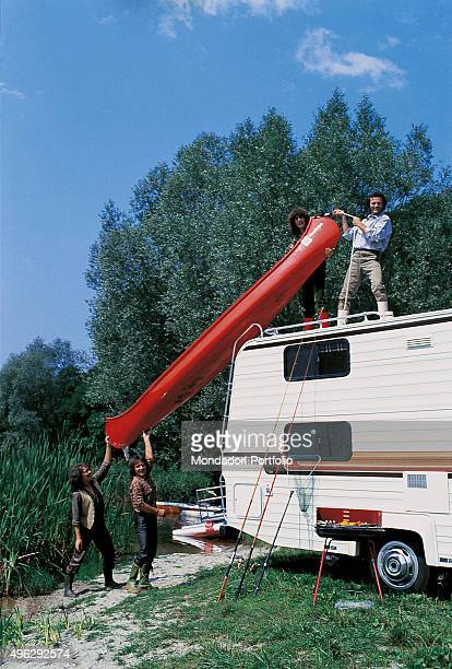 The members of Italian band The Pooh unloading a canoe from a camping van. Photocall. From the left Stefano D'Orazio; Red Canzian ; Roby Facchinetti...