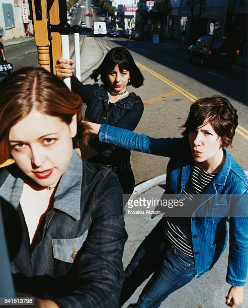 The members of the allgirl rock band SleaterKinney riding on a street car singer/guitarist Corin Tucker drummer Janet Weiss and singer/guitarist...