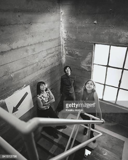The members of the allgirl rock band SleaterKinney standing in a stairway drummer Janet Weiss singer/guitarist Carrie Brownstein and singer/guitarist...