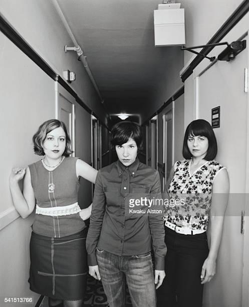 The members of the allgirl rock band SleaterKinney standing in a hallway singer/guitarist Corin Tucker singer/guitarist Carrie Brownstein and drummer...