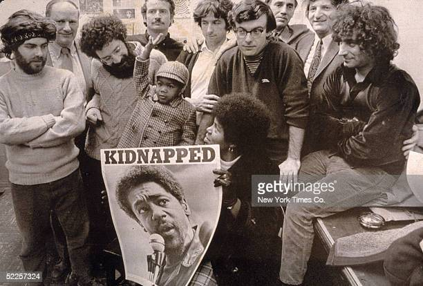 Jerry Rubin David Dellinger Lee Weiner John Froines Tom Hayden Rennie Davis Abbie Hoffman pose with others holding a poster of Bobby Seale that reads...