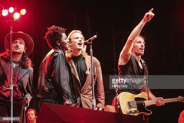 The members of the 'Human Rights Now' world tour sing together in a row at the Los Angeles show From left special LA guest Bono of U2 Tracy Chapman...
