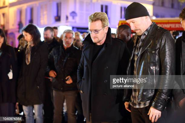 The members of the Irish rock band U2 Bono and David Howell Evans place flowers near the music and theatre venue Bataclan in Paris France 14 November...