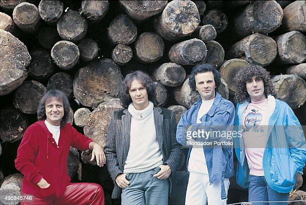 The members of the Italian band Pooh posing in front a pile of tree trunks From the left Roby Facchinetti Red Canzian Dodi Battaglia and Stefano...