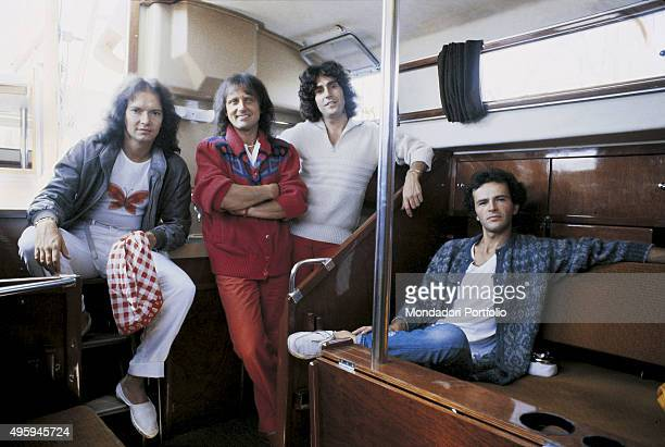 The members of the Italian band Pooh posing inside a boat during a photo shoot From the left Red Canzian Roby Facchinetti Stefano D'Orazio and Dodi...
