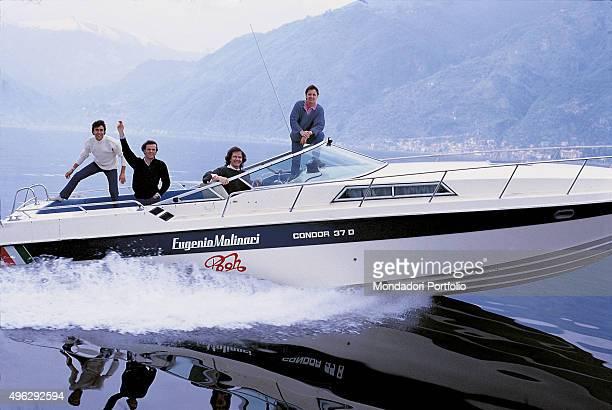 The members of the Italian band Pooh posing on a boat on a lake. From the left: Stefano D'Orazio, Dodi Battaglia , Red Canzian e Roby Facchinetti ....
