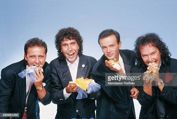 The members of the Italian band Pooh posing smiling and eating a piece of cake celebrating twenty years of career From the left Roby Facchinetti...