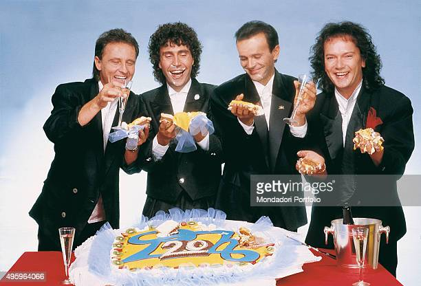 The members of the Italian band Pooh posing smiling with stem glasses and cake in their hands celebrating twenty years of career From the left Roby...
