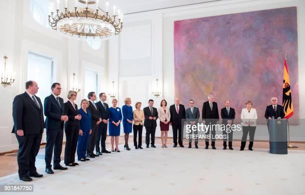 The members of the new Geman cabinet and German Chancellor Angela Merkel listen as German President FrankWalter Steinmeier delivers a speech during...