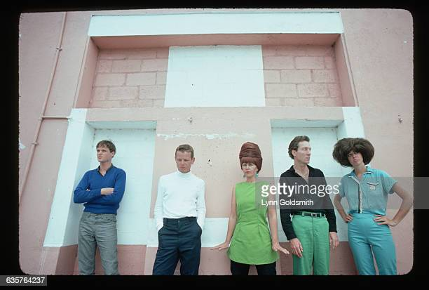 The members of the new wave band the B-52s pose against a wall.