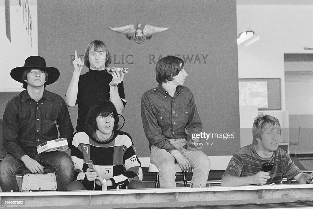 The members of the rock band Buffalo Springfield play with toy racing cars. The band is (from left to right): Rich Furay, Stephen Stills, Neil Young (seated), Bruce Palmer, and Dewey Martin.