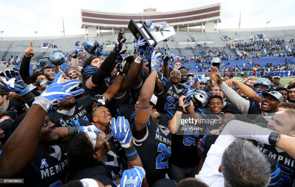 The Memphis Tigers celebrate and raise the West Division AAC Championship trophy after defeating the SMU Mustangs on November 18, 2017 at Liberty Bowl Memorial Stadium in Memphis, Tennessee. Memphis defeated SMU
