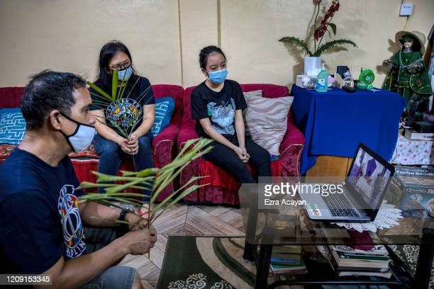 The Mendoza family holds palm fronds as they watch an online livestream of a Catholic mass on a laptop as they celebrate Palm Sunday inside their...