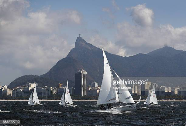 The mens 470 class fleet sail against the backdrop of Christ The Redeemer during training ahead of the Rio 2016 Olympic Games at the Marina da Gloria...