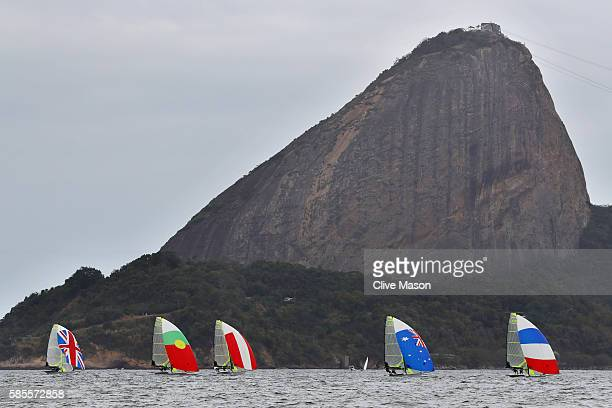 The Men's 49er fleet pass in front of Sugar Loaf mountain during a training session at Marina da Gloria on August 3 2016 in Rio de Janeiro Brazil