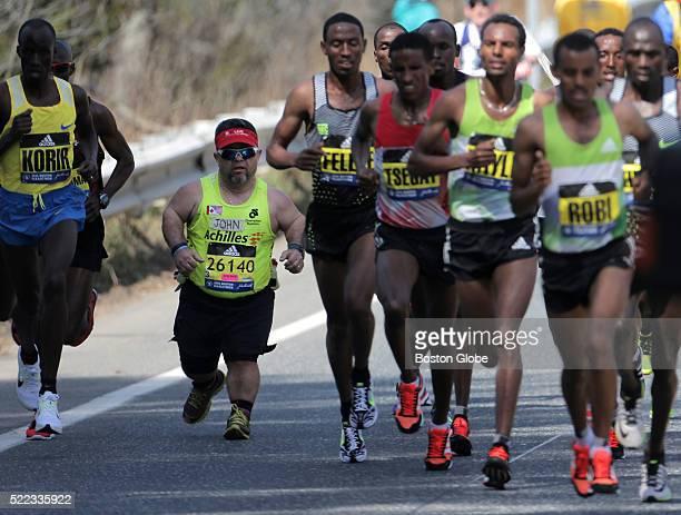 The men's elite pack passes runner John Young during the 120th Boston Marathon on Monday April 18 2016