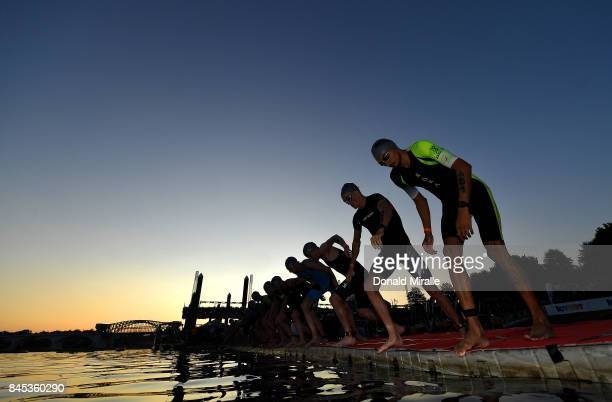 The Men's Professional Triathletes prepare to start with the sunrise on the Tennessee River with John Ross Bridge in the background during the Men's...