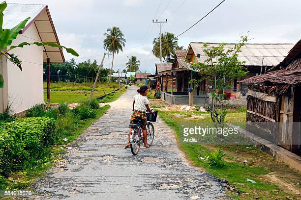 The Mentawai islands are a chain of 4 islands located 150 km off the western coast of Sumatra in Indonesia village and young girl on a bike in the...