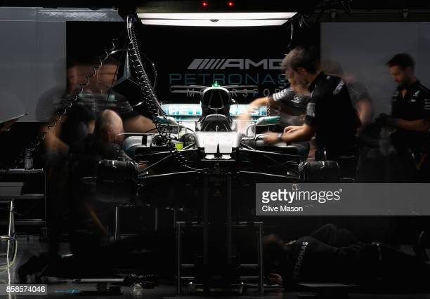 The Mercedes AMG team work on the car of Lewis Hamilton of Great Britain and Mercedes GP in the garage after qualifying for the Formula One Grand...