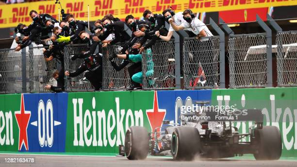 The Mercedes GP team celebrate on the pitwall as Lewis Hamilton of Great Britain driving the Mercedes AMG Petronas F1 Team Mercedes W11 crosses the...