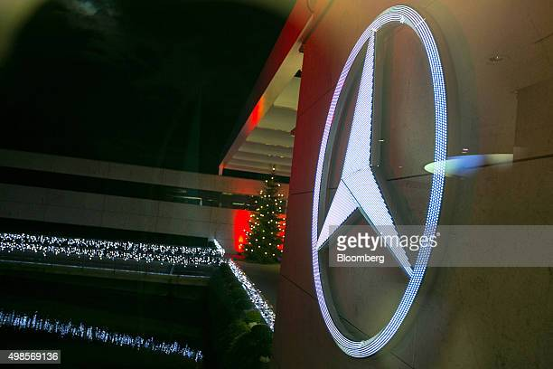 The MercedesBenz logo and a Christmas tree stand illuminated at night outside the center of excellence showroom at Daimler AG's MercedesBenz factory...