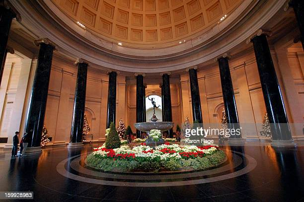 The Mercury fountain in the National Gallery of Art West building is surrounded by red and white flowers and lighted Christmas trees.
