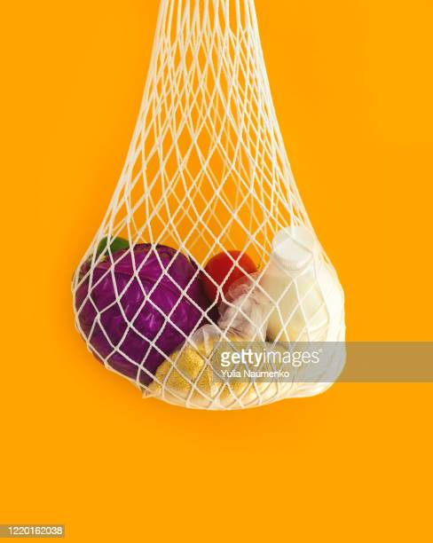 the mesh eco-shopping bag with with cereals, milk and vegetables on a yellow background. the modern reusable purchasing, the concept of zero waste. - 網状 ストックフォトと画像