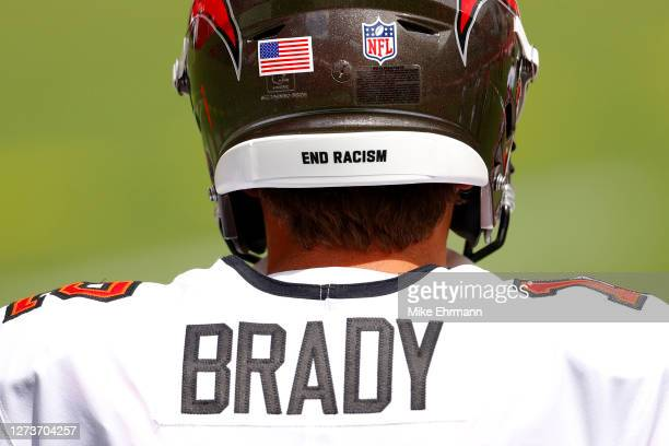 """The message """"End Racism"""" is seen on the helmet of Tom Brady of the Tampa Bay Buccaneers as he warms up before the game against the Carolina Panthers..."""