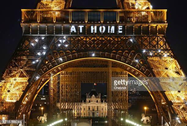 The message Stay at home is displayed on the Eiffel Tower at night to incite Parisians to stay at home during the Coronavirus epidemic on March 30...